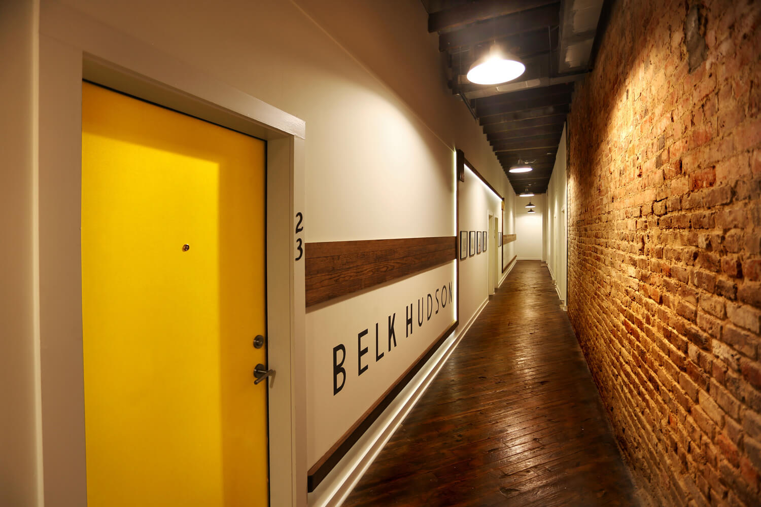 District 36 Lofts Designed by Foshee Architecture - View of Hallway with Wood Floors, Brick, and Exposed Wood Ceilings